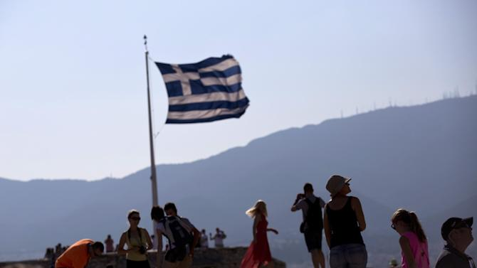 A Greek flag waves behind tourists at the ancient Acropolis hill, in Athens, on Tuesday, July 7, 2015. Greek Prime Minister Alexis Tsipras was heading Tuesday to Brussels for an emergency meeting of eurozone leaders, where he will try to use a resounding referendum victory to eke out concessions from European creditors over a bailout for the crisis-ridden country. (AP Photo/Petros Giannakouris)