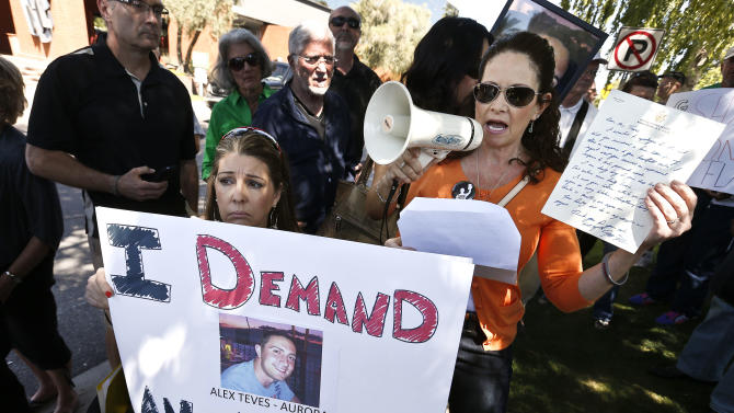 Caren Teves, right, whose son was killed in the Aurora, Colo., mass shooting, speaks as she holds up a handwritten letter to her from Sen. Jeff Flake, R-Ariz., as Jennifer Longdon, left, a shooting victim who was left paralyzed, holds up a protest sign as they join more than 50 anti-gun activists rallying outside Flake's office, Friday, April 19, 2013, in Phoenix.  Flake said Friday he wants Congress to expand background checks for firearm buyers, despite his recent vote against the Senate's bipartisan plan. (AP Photo/Ross D. Franklin)
