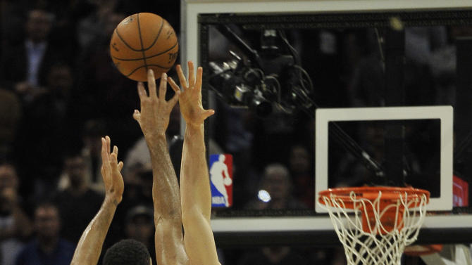 San Antonio Spurs forward Tim Duncan, left, sinks a basket over Memphis Grizzlies center Marc Gasol (33), of Spain, in the second overtime period, to send the game into triple overtime during an NBA basketball game, Wednesday, Dec. 17, 2014, in San Antonio. (AP Photo/Darren Abate)