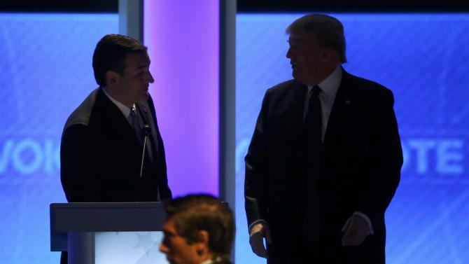Republican U.S. presidential candidate Senator Ted Cruz talks with rival candidate businessman Donald Trump as moderator David Muir looks on duriing a commercial break at