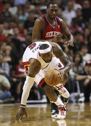 Miami Heat forward LeBron James, foreground, attempts to stay on his feet as he breaks for the basket trailed by Philadelphia 76ers forward Elton Brand during the first half of an NBA basketball game, Tuesday, April 3, 2012 in Miami. (AP Photo/Wilfredo Lee)
