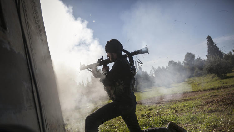 In this Saturday, Dec. 15, 2012 photo, a Free Syrian Army fighter fires a weapon during heavy clashes with government forces at a military academy besieged by the rebels north of Aleppo, Syria. Free Syrian Army fighters took control over the military academy after battling government forces for several hours. (AP Photo/Narciso Contreras)
