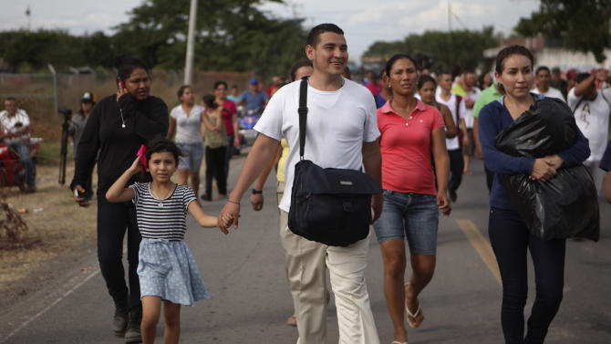 A vigilante walks holding his daughter's hand before leaving to voluntarily cooperate in a shootout investigation in La Ruana, Michoacan