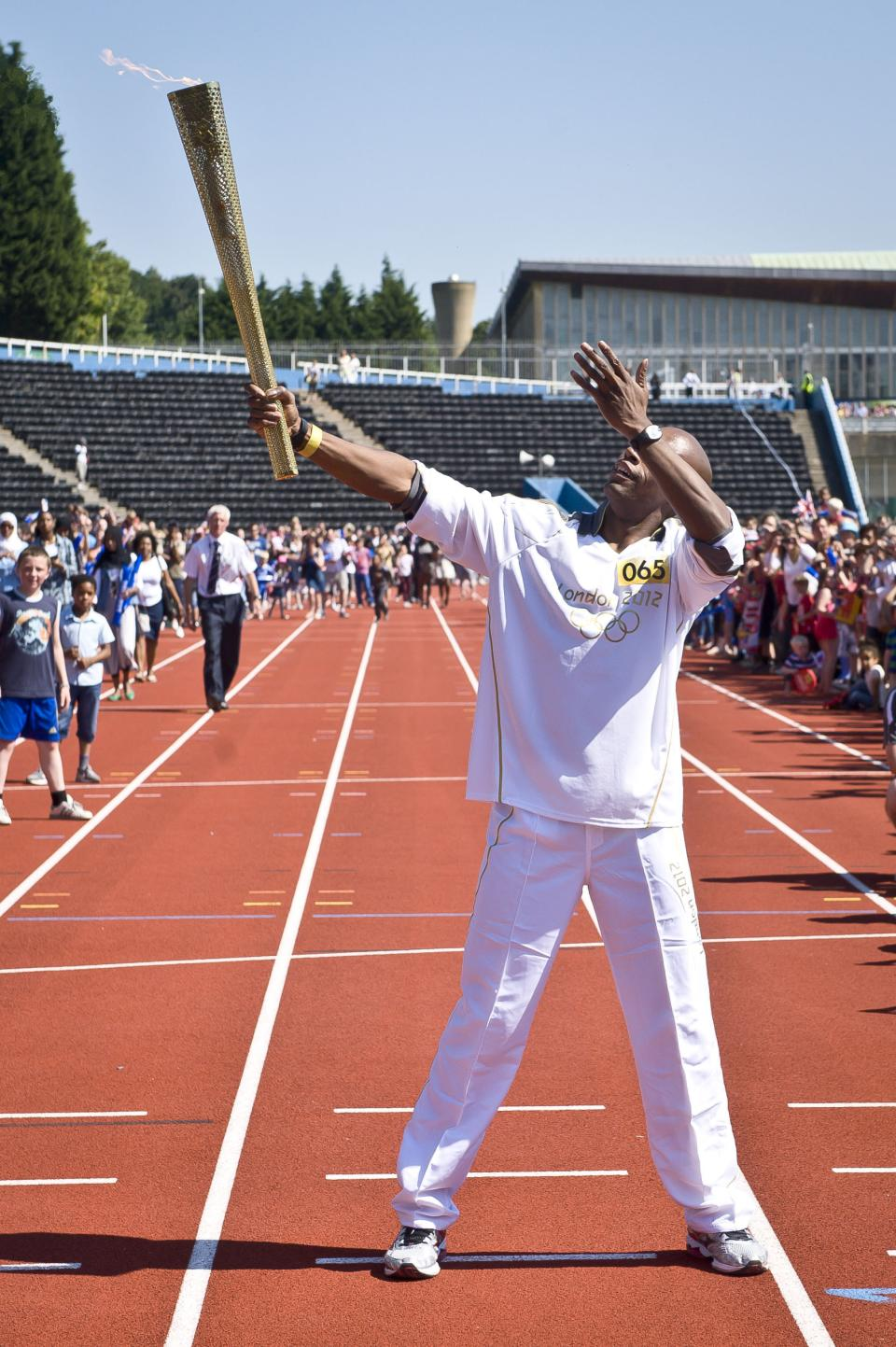 In this photo provided by LOCOG, Marlon Devonish carries the Olympic Flame at Crystal Palace stadium on the Torch Relay leg between Bromley and Croydon in London on Monday July 23, 2012. The opening ceremonies of the 2012 Summer Olympics are scheduled for Friday, July 27. (AP Photo/LOCOG, Ben Birchall)