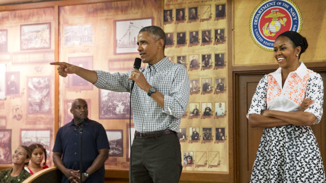 President Barack Obama, with first lady Michelle Obama, points toward a child in the audience as he greets troops and their families on Christmas Day, Thursday, Dec. 25, 2014, at Marine Corps Base Hawaii in Kaneohe Bay, Hawaii during the Obama family vacation. (AP Photo/Jacquelyn Martin)