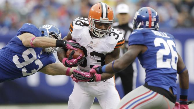 Cleveland Browns running back Trent Richardson (33) breaks a takle by New York Giants middle linebacker Chase Blackburn (93) as  Antrel Rolle (26) trails the play during the first half of an NFL football game Sunday, Oct. 7, 2012, in East Rutherford, N.J. (AP Photo/Kathy Willens)