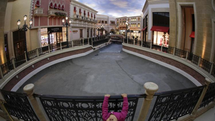 Three-year-old Luna Tasaki, of Tokyo, plays on a rail while walking along the water-drained canal with her parents at the Venetian hotel-casino, Thursday, Sept. 19, 2013, in Las Vegas. Management has closed the waterways for several weeks for maintenance. (AP Photo/Julie Jacobson)