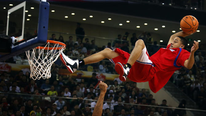 A stunt performer prepares to dunk during a break in the first of the NBA China Games between the Miami Heat and the Los Angeles Clippers at Wukesong arena in Beijing