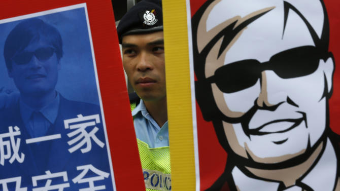 "A police officer stands guard in the middle of two images featuring blind Chinese activist Chen Guangcheng during a protest in front of the Chinese central government's liaison in Hong Kong Friday, May 4, 2012. Chen at the center of a diplomatic standoff between the United States and China said Friday his situation is ""dangerous,"" and that American officials have been blocked from seeing him for two days and friends who have tried to visit have been beaten up. (AP Photo/Vincent Yu)"