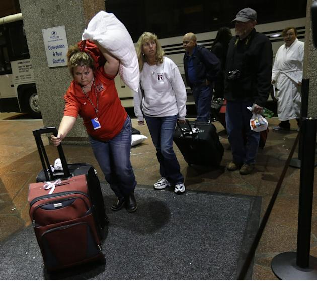 Passengers from the disabled Carnival Triumph cruise ship arrive by bus at the Hilton Riverside Hotel in New Orleans, Friday, Feb. 15, 2013.  The ship had been idled for nearly a week in the Gulf of M