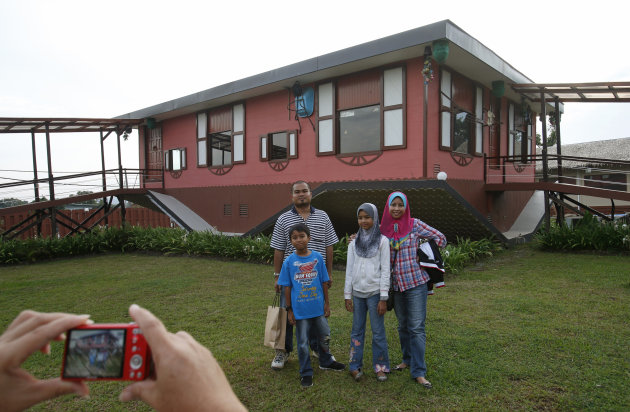 Tourists pose with an upside-down house in Tamparuli