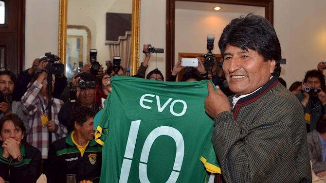 Bolivia's President Evo Morales holds a T-shirt of Bolivian national soccer team given to him by players during a visit to the presidential palace in La Paz