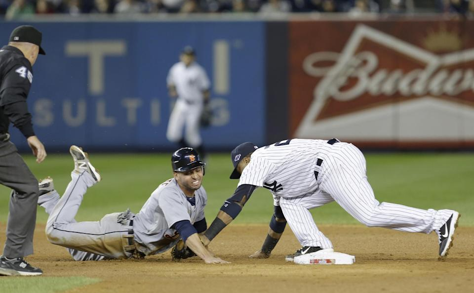 Detroit Tigers' Omar Infante dives back into second as New York Yankees' Robinson Cano reaches to tag him in the eighth inning of Game 2 of the American League championship series Sunday, Oct. 14, 2012, in New York. Infante was called safe on the play by umpire Jeff Nelson. (AP Photo/Paul Sancya )