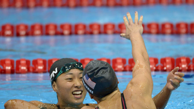 United States' Rebecca Soni, right, goes to embrace Japan's Satomi Suzuki after winning gold in the women's 200-meter breaststroke swimming final at the Aquatics Centre in the Olympic Park during the 2012 Summer Olympics in London, Thursday, Aug. 2, 2012. Soni set a new world record with a time of 2:19.59. (AP Photo/Mark J. Terrill)