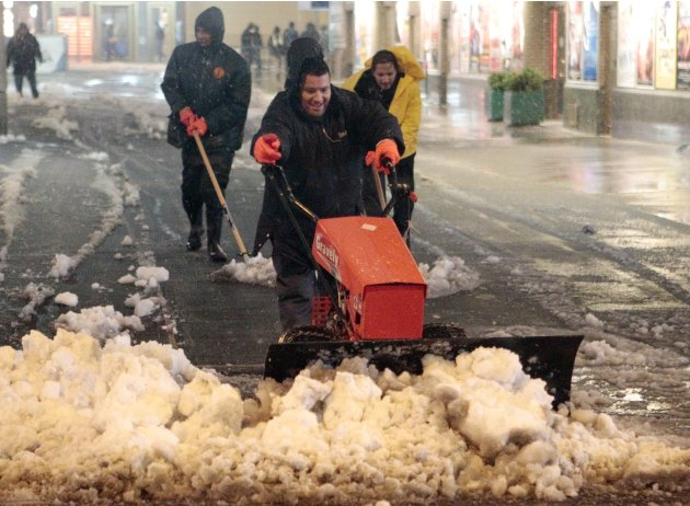 Men shovel snow from a walkway in Times Square Wednesday, Nov. 7, 2012, in New York. Coastal residents of New York and New Jersey faced new warnings to evacuate their homes and airlines canceled hundr