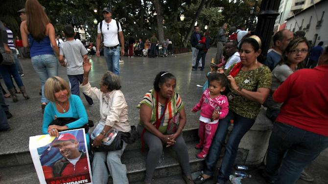 """Supporters of Venezuela's President Hugo Chavez, one of them holding a sign with an image of him, gather outside of the National Assembly during the  state-of-the-nation address in Caracas, Venezuela, Tuesday, Jan. 15, 2013. Venezuela's Vice President Nicolas Maduro submitted the report in writing from ailing President Hugo Chavez, who is receiving treatment in Cuba after undergoing his fourth cancer surgery. Opposition politicians had argued that lawmakers should have postponed the annual speech because Chavez was supposed to deliver it. The sign reads in Spanish """"Go ahead commander."""" (AP Photo/Fernando Llano)"""