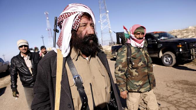 Yazidi fighters head to battle Islamic State militants, on the summit of Mount Sinjar, in Iraq, Sunday, Dec. 21, 2014. Iraqi Kurdish fighters pushed their way Sunday into the town of Sinjar, backed by U.S.-led coalition airstrikes against Islamic State militants who captured the town last summer. Loud explosions and intense gunbattles were heard from inside the town. (AP Photo/Dalton Bennett)