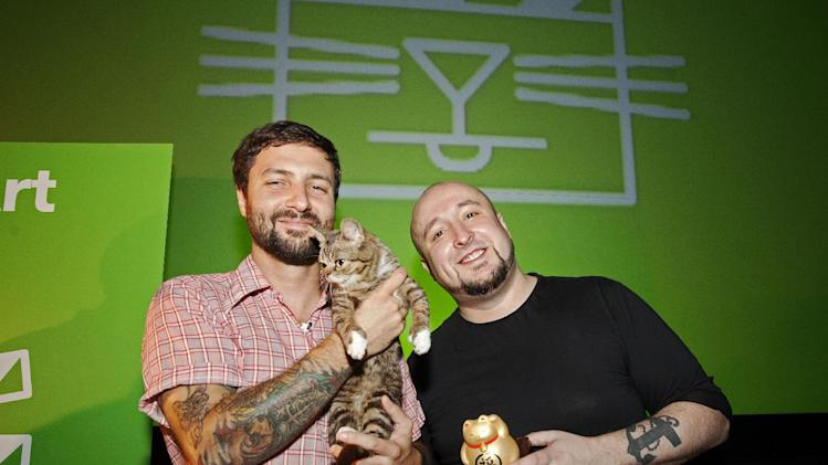 In this Aug. 30, 2012 publicity photo provided by the Walker Art Center, festival attendee, Mike Bridavsky and his cat Lil Bub, left, pose with Golden Kitty Award-winner William Braden, at the Walker Art Center Internet Cat Video Festival in Minneapolis. (AP Photo/Walker Art Center, Gene Pittman)
