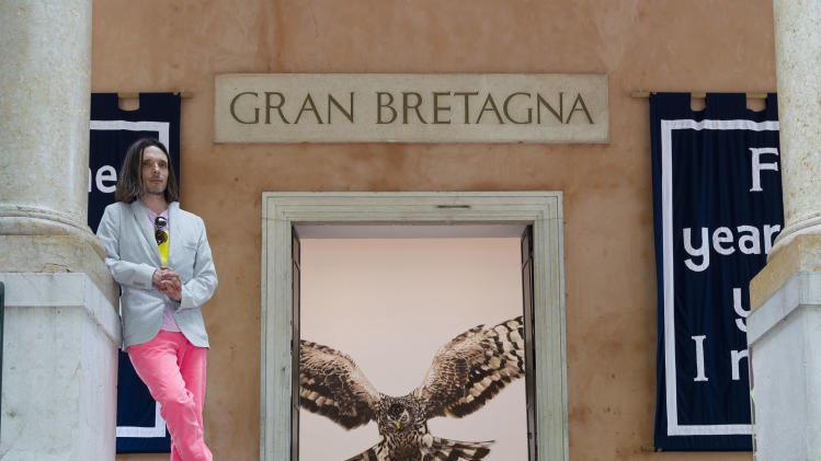 In this photo taken Wednesday, May 29, 2013, artist Jeremy Deller poses in front of the British Pavilion during a preview of the 55th edition of the Venice Biennale of Arts in Venice, northern Italy. The painting partially visible inside is Deller's 'The Sandringham Estate, Norfolk, UK 24 October 2007'. (AP Photo/Domenico Stinellis)