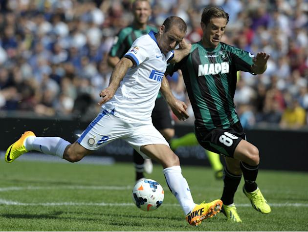 Sassuolo's Reto Ziegler of Switzerland, right, vies for the ball with Inter Milan's Rodrigo Palacio of Argentina, during their Serie A soccer match at Reggio Emilia's Mapei stadium, Italy, Sunday, Sep