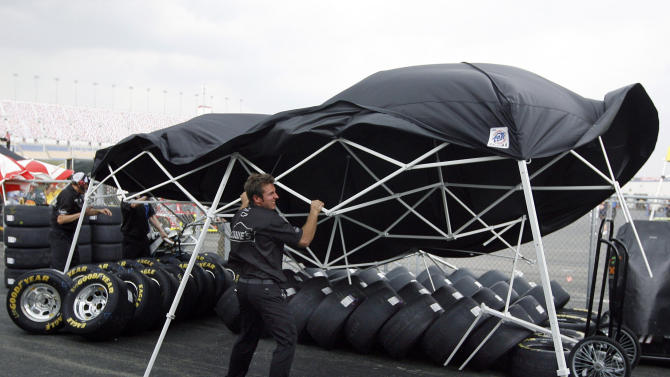 FILE - In this June 29, 2012, file photo, Pete Michel, crew member for Jimmie Johnson, tries to hold down a tent as a storm blows through prior to the scheduled start of the NASCAR Nationwide Series auto race at Kentucky Speedway in Sparta, Ky. A gigantic line of powerful thunderstorms with tree-toppling winds is likely to threaten one in five Americans Wednesday is as it rumbles from Iowa to Maryland, meteorologists warn. The massive storms may even spawn an unusual weather event called a derecho, which is a massive storm of strong straight-line winds spanning at least 240 miles.(AP Photo/James Crisp, File)