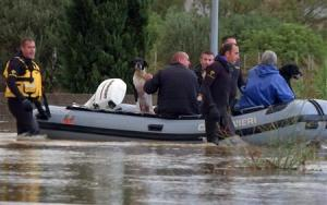 Rescue workers pulling a boat along, wade on a flooded street at San Gavino Monreale in Sardinia island
