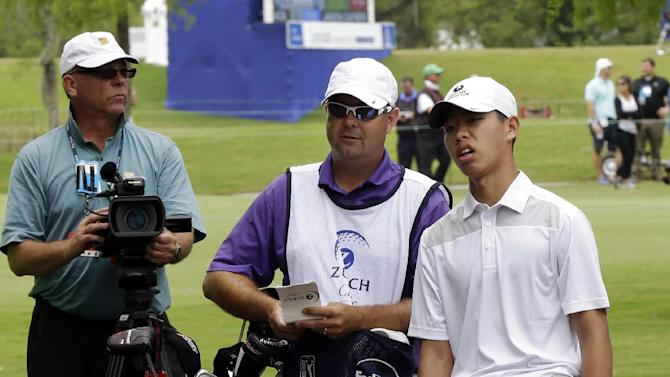 Guan Tianlang, 14, of China, eyes his shot after landing in the tree line on the first hole during the first round of the PGA Tour Zurich Classic golf tournament at TPC Louisiana in Avondale, La., Thursday, April 25, 2013. (AP Photo/Gerald Herbert)