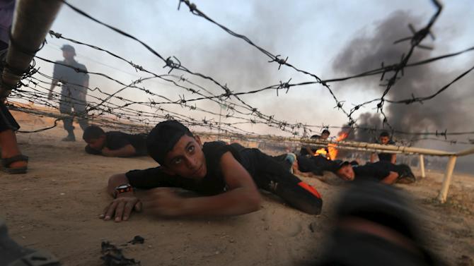 Young Palestinians crawl under an obstacle during a military-style exercise at Liberation Youths summer camp, organised by the Hamas movement, in Rafah in the southern Gaza Strip