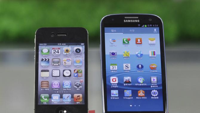Samsung Electronics' Galaxy S III, right, and Apple's iPhone 4S are displayed at a mobile phone shop in Seoul, South Korea, Friday, Aug. 24, 2012. South Korea's Samsung won a home court ruling in its global smartphone battle against Apple on Friday when Seoul judges said the company didn't copy the look and feel of the U.S. company's iPhone, and that Apple infringed on Samsung's wireless technology. However, in a split decision on patents, the panel also said Samsung violated Apple technology behind the bounce-back feature when scrolling on touch screens, and ordered both sides to pay limited damages. (AP Photo/Ahn Young-joon)