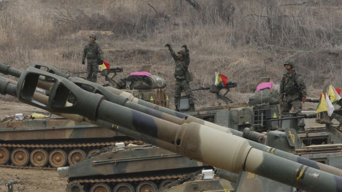 South Korean marines stand on K-55 self-propelled howitzers during an exercise against possible attacks by North Korea near the border village of Panmunjom in Paju, South Korea  Monday, April 1, 2013.  After weeks of war-like rhetoric, North Korean leader Kim Jong Un gathered legislators Monday for an annual spring parliamentary session taking place one day after top party officials adopted a statement declaring building nuclear weapons and the economy the nation's top priorities.(AP Photo/Ahn Young-joon)