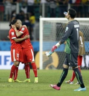 Switzerland's Ricardo Rodriguez, left, hugs Blerim Dzemaili following the team's 5-2 loss to France during the group E World Cup soccer match between Switzerland and France at the Arena Fonte Nova in Salvador, Brazil, Friday, June 20, 2014. (AP Photo/Natacha Pisarenko)