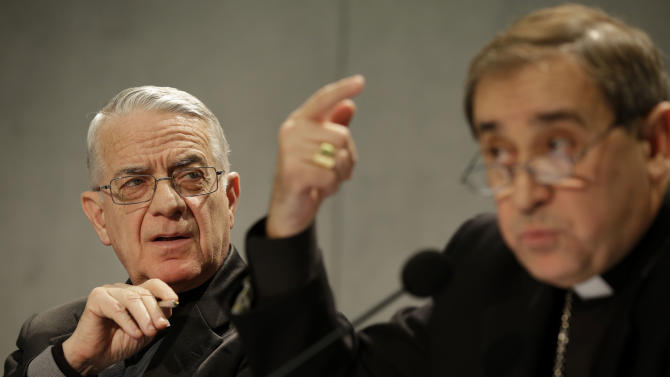Bishop Juan Ignacio Arrieta, right, flanked by Vatican spokesman, Rev. Federico Lombardi, gestures during a press conference at the Vatican, Friday, Feb. 22, 2013. Pope Benedict XVI may enact a new law governing the upcoming conclave to elect a new pope amid continued uncertainty over when the voting can begin. Lombardi, said Wednesday that he didn't know for sure if the new law under consideration would address the timing of the conclave following Benedict's Feb. 28 resignation. (AP Photo/Gregorio Borgia)