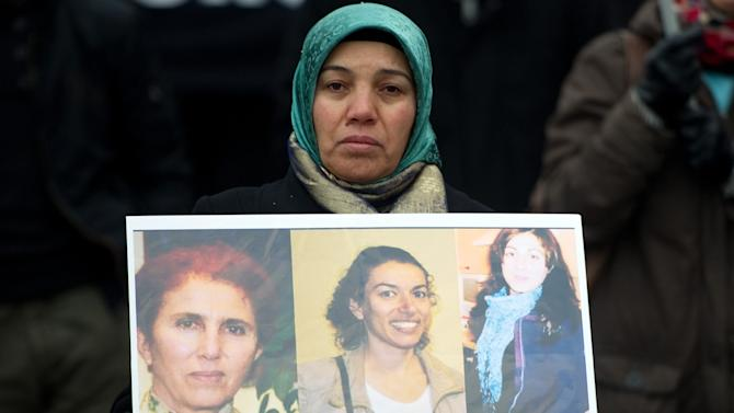 A woman hold pictures of three murdered female Kurdish activists during a demonstration of Kurdish organizations in Hamburg, northern Germany, Jan. 11, 2013. The demonstration took place because of the shooting of three female Kurdish activists in Paris, Jan. 9, 2013. (AP Photo/dpa, Axel Heimken)