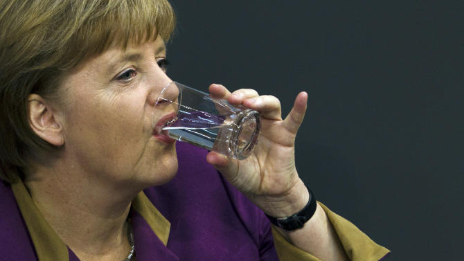 "German Chancellor Angela Merkel drinks water after her speech prior to the debate and the voting of the German Parliament Bundestag about a new Greek rescue package Berlin, Germany, Monday, Feb. 27, 2012. Merkel urged German lawmakers to support the new rescue package on, though she conceded that there is no ""100 percent guarantee"" it will succeed. (AP Photo/Markus Schreiber)"