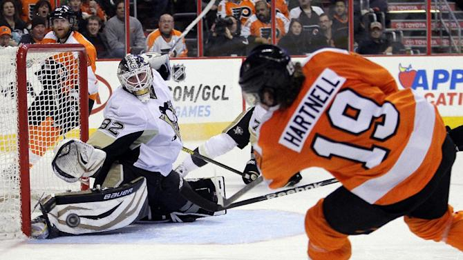 Philadelphia Flyers' Scott Hartnell, right, takes a wrist shot at Pittsburgh Penguins goalie Tomas Vokoun who deflected the puck in the second period of an NHL hockey game, Thursday, March 7, 2013, in Philadelphia. (AP Photo/Tom Mihalek)