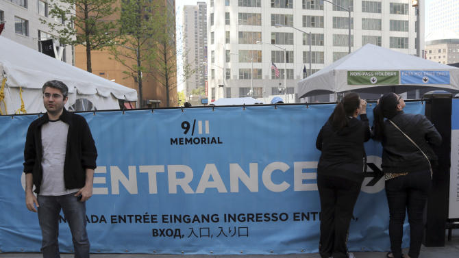 A visitor to the Sept. 11 Memorial, left, poses for a photo as others, right, peer at the entrance line, Saturday, May 4, 2013, in New York. Faced with hefty operating costs, the foundation building the underground 9/11 museum at the World Trade Center has decided to charge a mandatory admission fee of $20 to $25 when the site opens next year. Entry to the memorial plaza with its twin reflecting pools will still be free, but the decision to charge for the underground museum housing relics of the terror attacks has been greeted with dismay by some relatives of trade center victims. (AP Photo/Mary Altaffer)
