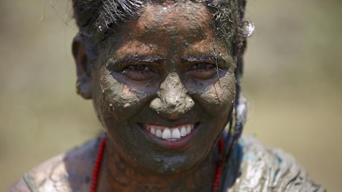 A woman covered in mud smiles during the Asar Pandhra festival in Pokhara