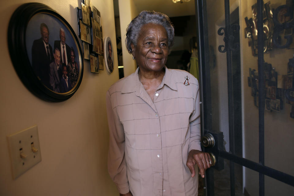 In this photo taken Monday, July 8, 2013, Thelma Gibson, 86, stands in the doorway of her home in the Village West neighborhood of Coconut Grove in Miami. Gibson's grandfather was among the Bahamian immigrants who settled in the area in the 1880's. (AP Photo/Lynne Sladky)