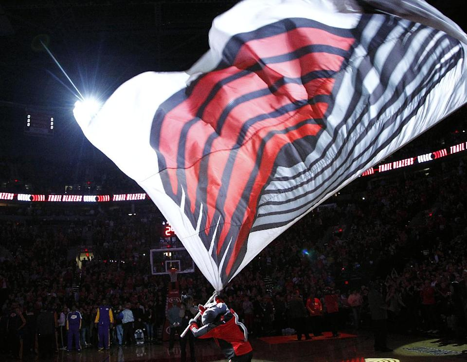 The Portland Trail Blazers' mascot, Blaze, waves a large flag with the Blazers emblem on it at mid-court before the team's NBA basketball season opener against the Los Angeles Lakers in Portland, Ore., Wednesday, Oct. 31, 2012. (AP Photo/Don Ryan)