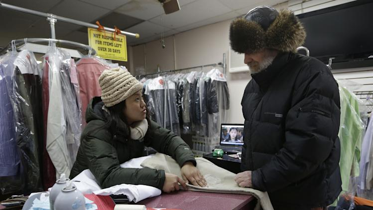 FILE - In this file photo of Jan. 24, 2013, dry cleaning employee Xiao Mei Zhang wears a down coat and wool hat indoors to keep warm in the absence of heat as she talks to customer Beso Khomeroke about cleaning his oil-stained pants in New York. The Rockaways store where Zhang works hasn't had heat since Superstorm Sandy. While businesses have begun reopening and communities plow ahead with rebuilding, fatigue and frustration have set in over the painfully slow recovery process. (AP Photo/Kathy Willens, File)