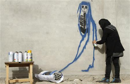 Afghan artist Malina Suliman paints graffiti on a wall in Kandahar city