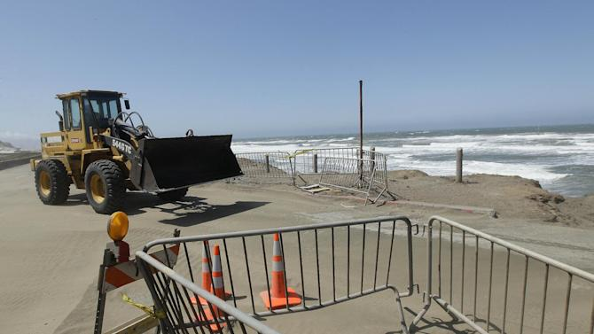 In this photo from Thursday, May 24, 2012, a construction vehicle moves sand near the parking lot at Ocean Beach is shown in San Francisco. In San Francisco, officials are mulling a significant retreat on its western flank, where the Great Highway is under assault from the Pacific Ocean. Right now, a beach parking lot that abuts the highway is crumbing into the sea just across the highway from the San Francisco Zoo. (AP Photo/Jeff Chiu)