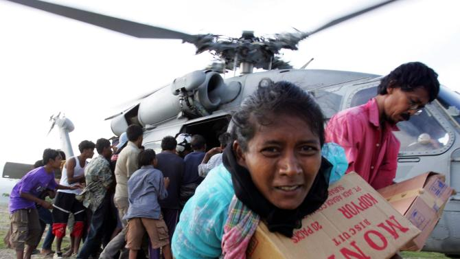 File photo of tsunami refugees receiving supplies distributed by USS Abraham Lincoln carrier strike group in Krueng Raya