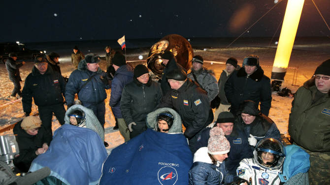 International Space Station crew members Russian astronaut Yury Malenchenko, center, U.S. astronaut Sunita Williams, right, and Japanese astronaut Aki Hoshide, left, rest shortly after landing in a Soyuz capsule outside the town of Arkalyk, Kazakhstan, on Monday, Nov. 19, 2012. The three astronauts touched down in the dark, chilly expanses of central Kazakhstan onboard a Soyuz capsule Monday after a 125-day stay at the International Space Station. (AP Photo/Maxim Shipenkov, Pool)