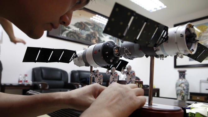 A Chinese official arranges astronaut figures with a scale model of the Shenzhou 9 module docking with China's Tiangong 1 space module to present them at a press conference at the Jiuquan satellite launch center near Jiuquan in western China's Gansu province, Friday, June 15, 2012. China will launch three astronauts, including a mother of one who flies transport planes, to live and work on a space station for about a week, a major step in its goal of becoming only the third nation with a permanent base orbiting Earth. (AP Photo/Ng Han Guan)