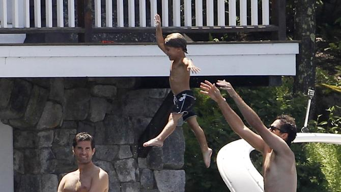 Republican presidential candidate, former Massachusetts Gov. Mitt Romney, watches as his grandson Miles is tossed into the lake by Craig Romney, right, on Lake Winnipesaukee in Wolfeboro, N.H., Friday, July 6, 2012, as he continues his vacation from the campaign trail. Also pictured are son Matt Romney, standing left, and Josh Romney, seated second left. (AP Photo/Charles Dharapak)