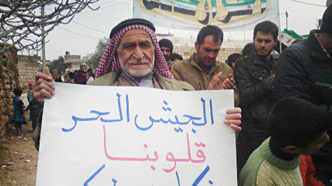 """In this citizen journalism image provided by the Local Coordination Committees in Syria and released Wednesday, Feb. 1, 2012, an anti-Syrian regime protester, holds a poster in Arabic that reads, """"to the Syrian freedom soldiers, our hearts are bases for you,"""" as he walks during a demonstration in Idlib Province, north Syria. Russia's deputy defense minister says Moscow will not stop arms sales to Syria. Russian state news agencies quoted Deputy Defense Minister Anatoly Antonov on Thursday as saying Russia is not violating any international obligations. (AP Photo/Local Coordination Committees in Syria)  THE ASSOCIATED PRESS IS UNABLE TO INDEPENDENTLY VERIFY THE AUTHENTICITY, CONTENT, LOCATION OR DATE OF THIS HANDOUT PHOTO"""