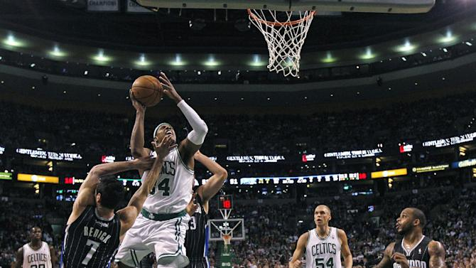Boston Celtics forward Paul Pierce (34) drives to the basket against Orlando Magic guard J.J. Redick (7) during the second quarter of an NBA basketball game in Boston, Wednesday, April 18, 2012.  At right are Celtics center Greg Stiemsma (54) and Magic guard Jameer Nelson (14). (AP Photo/Charles Krupa)