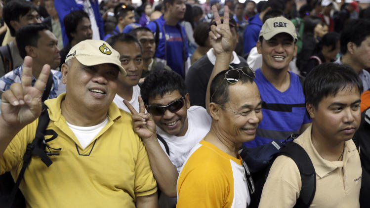 """Overseas Filipinos who were working at the sprawling oil field in Algeria which was attacked by terrorists, flash the """"V"""" sign as they queue up at the Philippine Immigration upon arrival Sunday, Jan. 20, 2013 at the Ninoy Aquino International Airport in Manila, Philippines. The Department of Foreign Affairs in their statement, said that 39 Filipino workers, out of the 52 accounted for following the Algerian hostage crisis, arrived after being evacuated from Algeria via Palma de Mallorca in Spain. The workers claimed they were hundreds of kilometers away from the hostage-taking site but ordered evacuated. (AP Photo/Bullit Marquez)"""