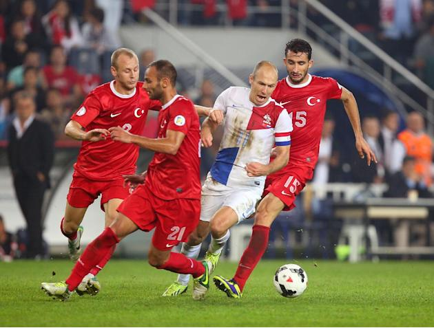 Turkey's Omer Toprak, second left, and Semih Kaya, left, fight for the ball with Arjen Robben of Netherlands, second right, during their World Cup Group D qualifying soccer match at Sukru Saracoglu St
